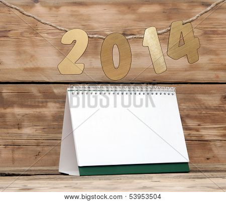 two thousand fourteen New Year number decoration hanging on rope over blank desk calendar