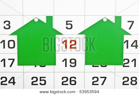 two shape green houses on a calendar background, paying your mortgage on time