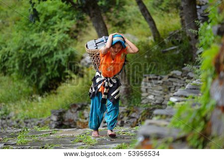 A young Gurung woman carrying a basket in the Himalayas