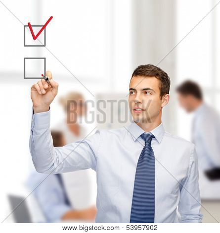business and office concept - attractive buisnessman or teacher with marker drawning red checkmark into checkbox