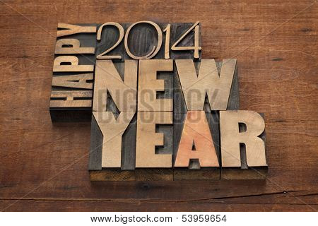 Happy New Year 2014 greetings - text in vintage letterpress wood type blocks on a grunge wooden background
