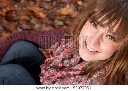 Smiling Girl On The Autumn Ground