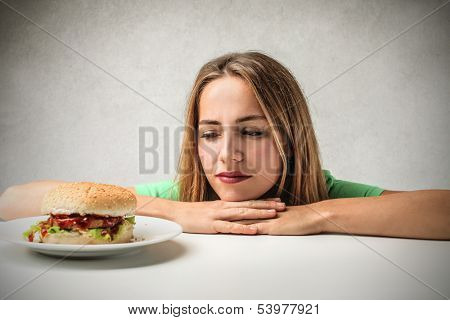 beautiful woman looking with desire a tasty hamburger