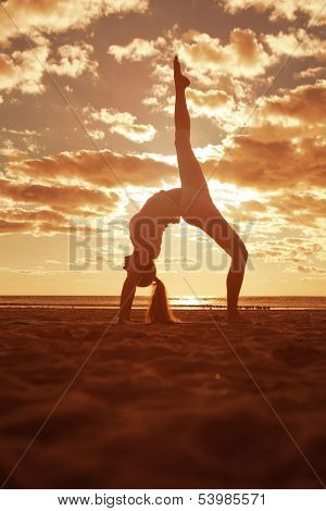 Young beautiful slim woman silhouette practices yoga on the beach at sunset. Yoga at  sunrise