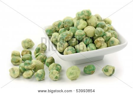 Wasabi peas on white plate isolated on white background