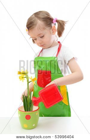 Little girl watering daffodil with a watering can toy