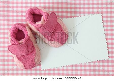 Baby shoes and blank note on pink background