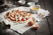 stock photo of oregano  - Stretched and uncooked homemade pizza dough with tomato sauce and mozzarella on a kitchen towel ready for ingredients. Taken on a rustic dark wooden table with flour rolling pin salt oregano and egg.