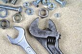 image of big-rig  - Wrench, monkey wrench and various bolts and nuts on particle board .