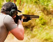 stock photo of shotguns  - Man in heaphones and cap shoot with shotgun - JPG
