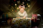 stock photo of solemn  - one-year-old little girl solemnize Christmas sit under Christmas-tree and reach gift of box horizontal photo