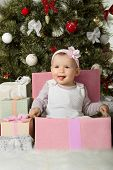 image of solemn  - one-year-old little girl solemnize Christmas sit under Christmas-tree with gift vertical photo