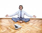 picture of mudra  - Indian businessman listening the music with headphones and doing yoga near the laptop in the office at white background - JPG