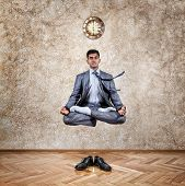 stock photo of levitation  - Levitation by Indian businessman in lotus pose in the office near the wall with clock and his shoes on the floor - JPG