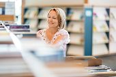 image of librarian  - Mature female librarian working in library - JPG