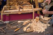 image of work bench  - Artisan hands at work carving wood into spoons - JPG