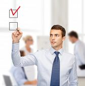 business and office concept - attractive buisnessman or teacher with marker drawning red checkmark i