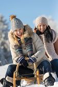 stock photo of luge  - Two female friends sledge downhill in wintertime sunny snow day - JPG