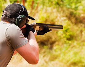 picture of shotgun  - Man in heaphones and cap shoot with shotgun - JPG