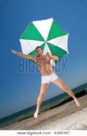 Bizarre Young Man With Umbrella On A Beach