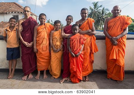 GALLE, SRI LANKA - MARCH 9, 2014: Group of buddhist monks wearing traditional orange robes. Galle is home of Fort Shri Sudarmalaya Buddhist Temple.