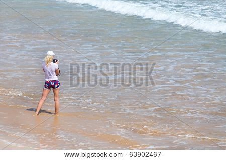 WELIGAMA, SRI LANKA - MARCH 7, 2014: Young tourist stands on sandy beach and taking photos of the sea. Tourism and fishing are two main business in this town.