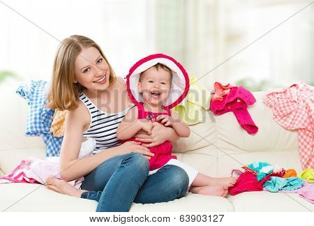 Happy  Mother And Baby Girl With Clothes Ready For Traveling On Vacation
