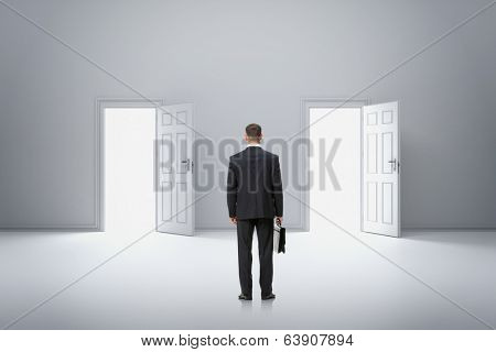 Full-length backview portrait of businessman with case in front of two doors. Concept of hard choice and difficulties