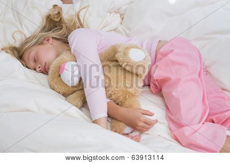 Young girl sleeping peacefully with stuffed toy in bed at home