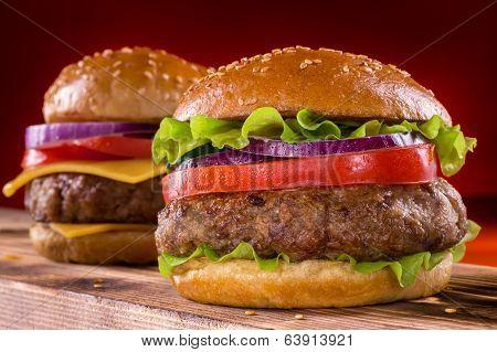 Cheeseburger and Hamburger on wood background.