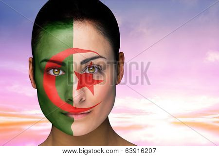 Composite image of beautiful brunette in algeria facepaint against beautiful blue and yellow sky