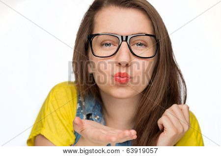 Teenage girl in geek glasses blowing kiss on white background