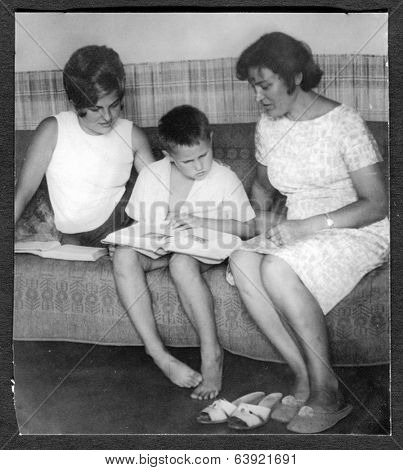 Poland, circa 1969: mother and son with her friend talking and showing photographs, circa 1969