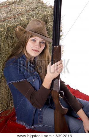 Mulher segurando a arma sentado no cobertor vermelho