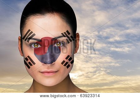 Composite image of beautiful brunette in south korea facepaint against scenic landscape with blue cloudy sky