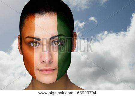 Composite image of beautiful brunette in ivory coast facepaint against bright blue sky with clouds