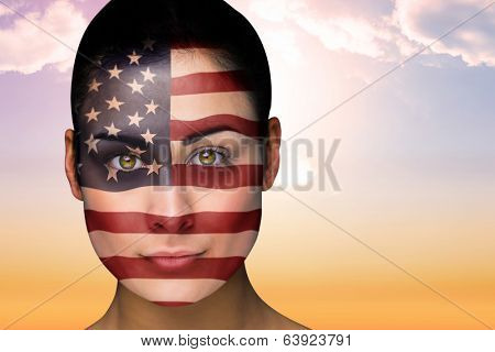 Composite image of beautiful brunette in america facepaint against beautiful orange and blue sky