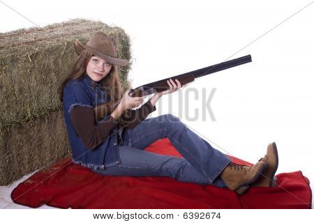 Woman Sitting Against Hay Holding Shotgun