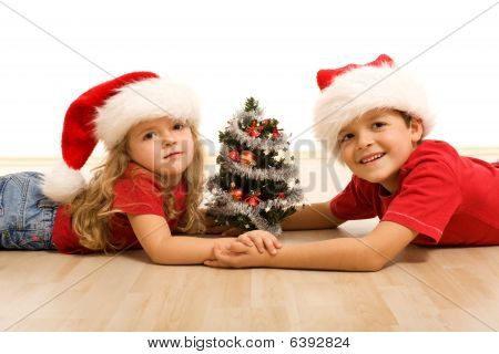Kids On The Floor With A Decorated Tree And Christmas Hats