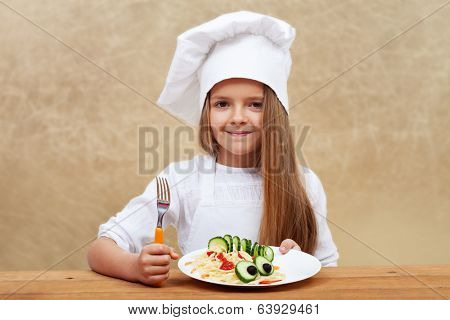 Happy child with chef hat holding pasta dish with cucumber creature decoration