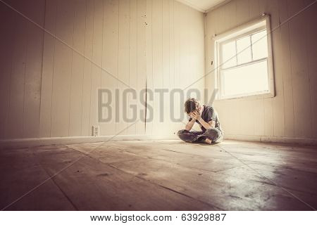 Sad boy alone in a bare room