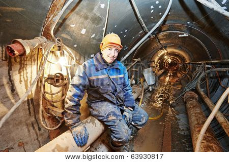 Tunneller sinker worker connecting equipment in tunnel of sewer collector at undergroung working