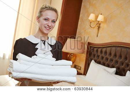 Hotel service. female chambermaid or housekeeping worker with towels and bedclothes at inn room