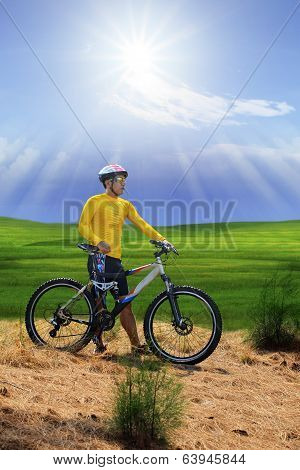 Young Man Standing Beside Moutain Bike  On Hill With Sun Shining On Blue Sky