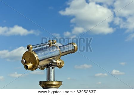 coin operated antique telesecope with brass and metal elements in front of a blue cloudy sky
