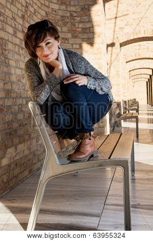 Beautiful Young Woman Posing On A Bench