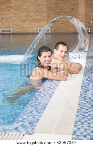 Smiling man and woman in swimming pool