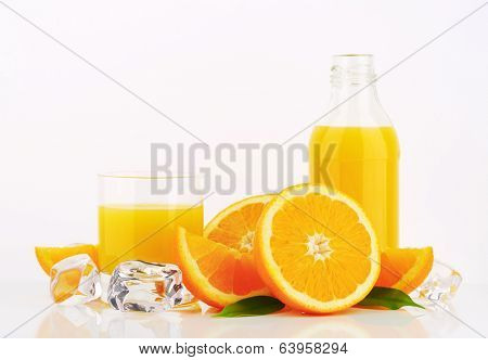 orange juice in the glass and bottle with fresh pieces of oranges and ice cubes