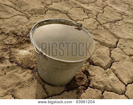 bucket full of water on dry cracked soil background