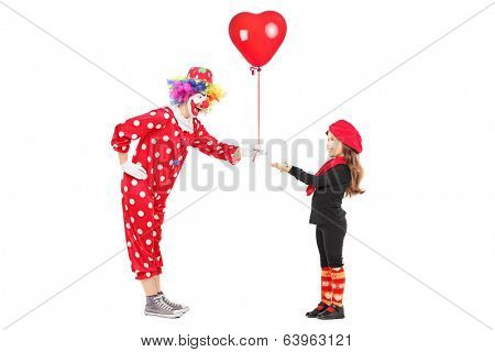 Male clown giving a red balloon to a little girl isolated on white background